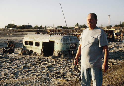 Man stands next to his mobile home in the desert