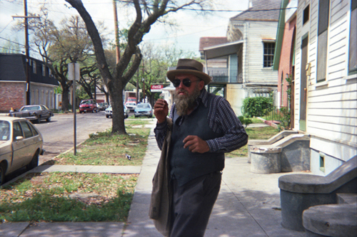 Poppa Neutrino walking down a suburban street wearing a hat