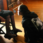 Teenage girl kneeling in front of wheelchair