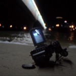 A video camera lies in the sand at the beach at night