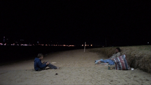 Teenage boy with a video camera films a derelict on a beach at night