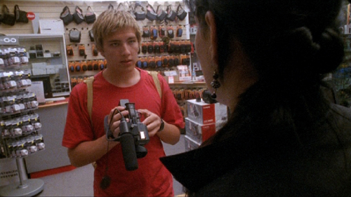 Teenage boy shops for a video camera in a store