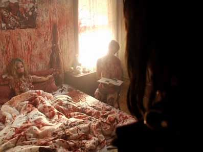 Female serial killer victim lies in a blood soaked bed