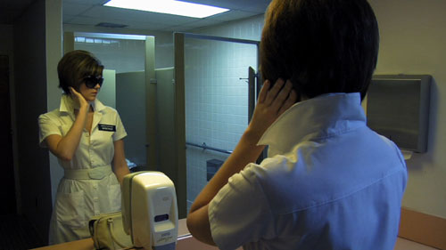Nurse wearing sunglasses fixes her hair in the mirror