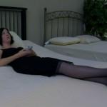 Woman wearing a dress lies down on a mattress in a store
