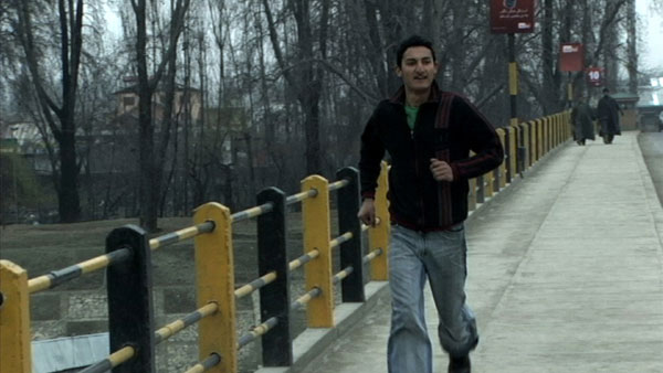 Kashmir man runs across a bridge