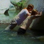 Two men doing push-ups against a rock in a pond