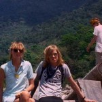 Three young adults hang out on an overlook in the jungle
