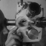 Man Ray adjusts the lens on his camera