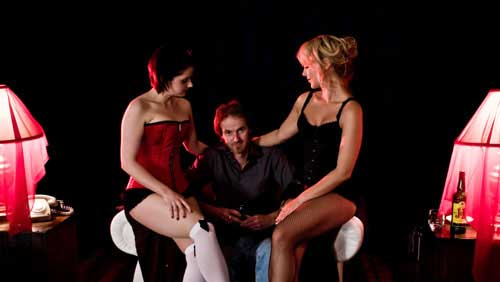 Grungy man flanked by two gorgeous women in lingerie