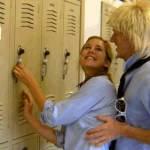 Teenage boy gropes girl at high school locker