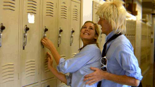 Teenage boy gropes girl at high school locker