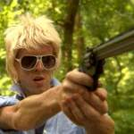 Teenage boy with sunglasses pointing a gun