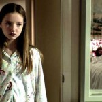 Young girl in pajamas looks in a mirror at the corpse of an older woman