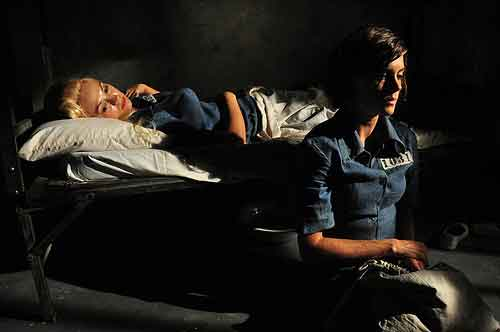 Female prisoner lies in her cot while cellmate sits nearby