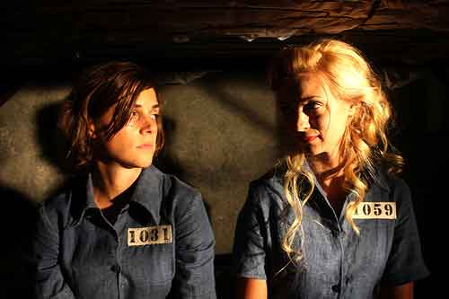 Two pretty female convicts sit in their jail cell
