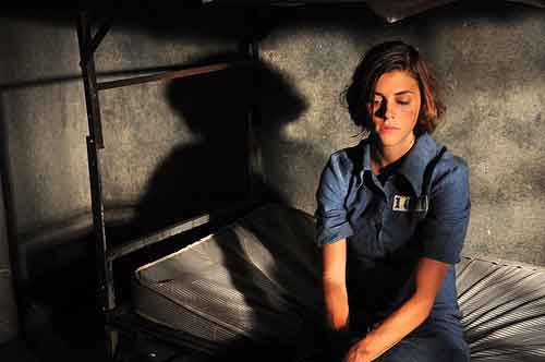 Female convict sits on her bunk