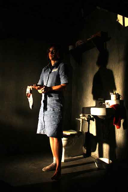 Female prisoner stands by the toilet in her jail cell