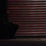 Man sits against a garage door