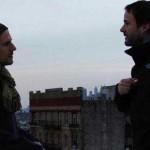 Two male friends talk on an urban rooftop
