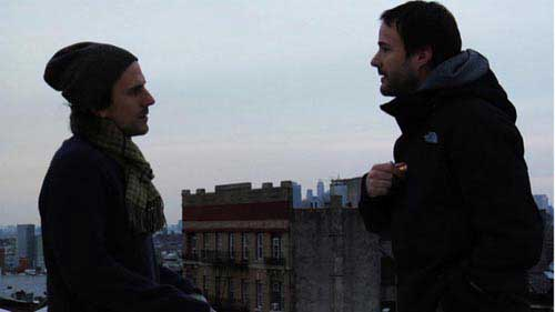Two male friends talk on an urban rooftop