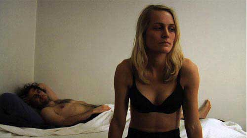 Man lies in bed while woman in bra looks forlorn