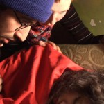 Man wearing winter hat tries to wake up a sleeping woman