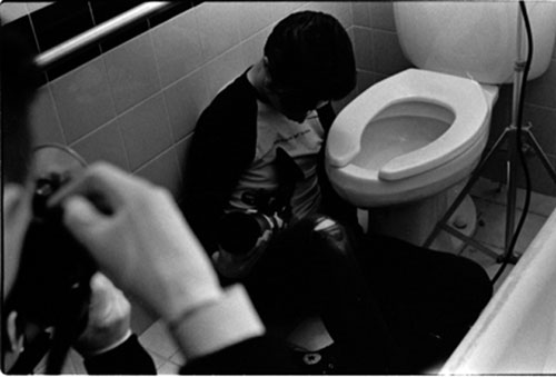 Cinematographer sits on the floor of a bathroom