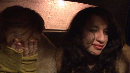Two women sit close to each other in the backseat of a taxi cab