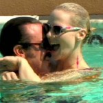 Man cuddles a woman in a swimming pool