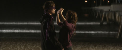 Girl puts blindfold on boy on the beach at night