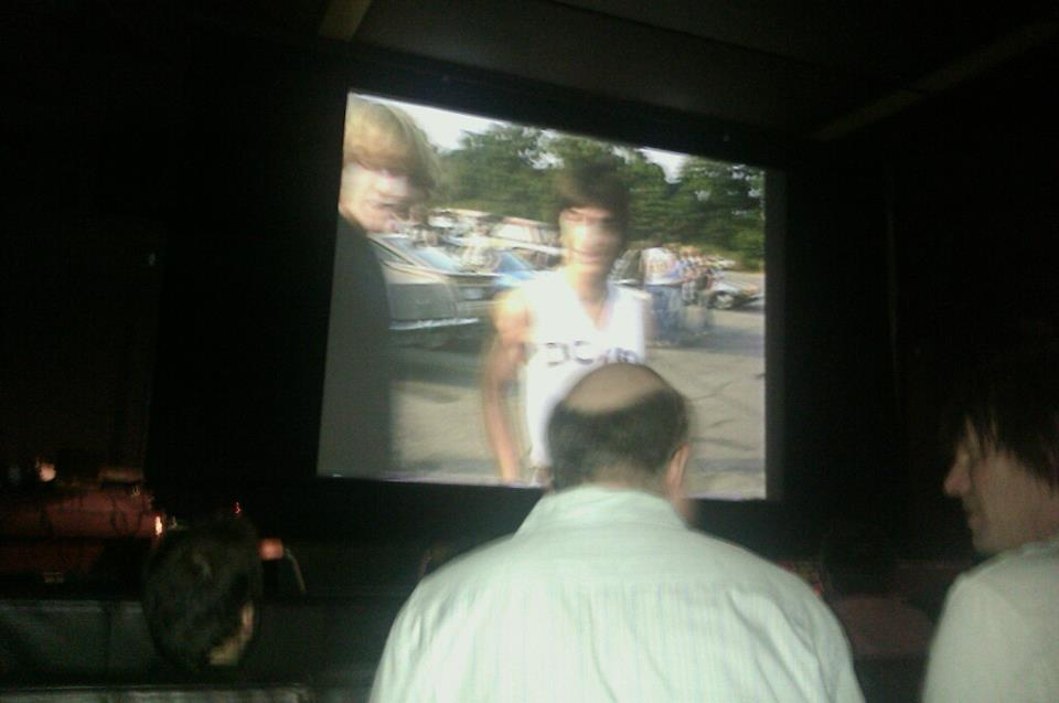 The back of filmmaker Jeff Krulik's head while his film plays on-screen
