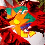 Two teenage girls in red dressed dance in front of artwork