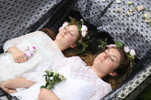 Two teenage girls wearing white dresses pretend to be corpses in a funeral boat