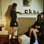 Two teenage girls dressed in schoolgirl outfits look morose
