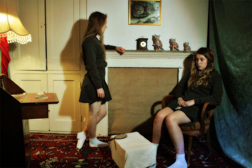Two teenage girls dressed in schoolgirl outfits look morose