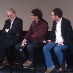 On stage, Joel and Ethan Cohen listen to T-Bone Burnett answer a question