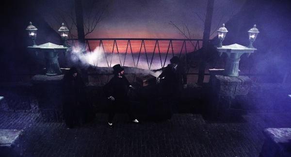 19th century men stand on a foggy bridge