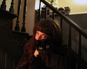 Filmmaker Christine Lucy Latimer hugs her black cat Mingus in front of a staircase