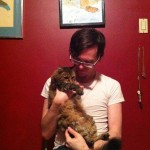 Clint Enns sits in front of a red wall while holding his fluffy cat Mia
