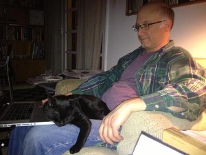 Filmmaker Jeff Krulik tries to work on his laptop while his black cat Iggy sleeps on his legs