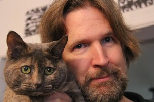 Filmmaker Skizz Cyzyk holds up his cat Speck, who has a concerned look on her face