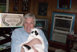 Filmmaker Vic Zimet sits in front of his computer workstation while holding his white cat Fidget
