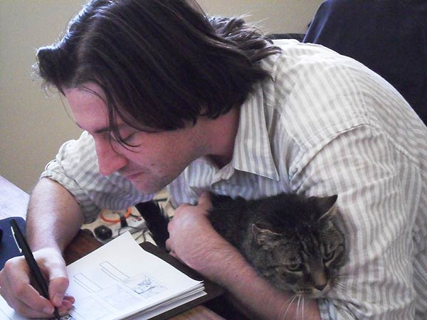 Filmmaker Waylon Bacon draws storyboards for his next film while his cat Lou Rawls keeps him company