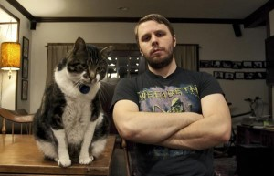 Filmmaker Brady Hall, wearing a Megadeth T-shirt, sits with his arms crossed next to his large cat Reggie