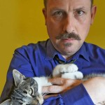 British filmmaker Duncan Reekie cradles his striped cat Tikky in his arms.