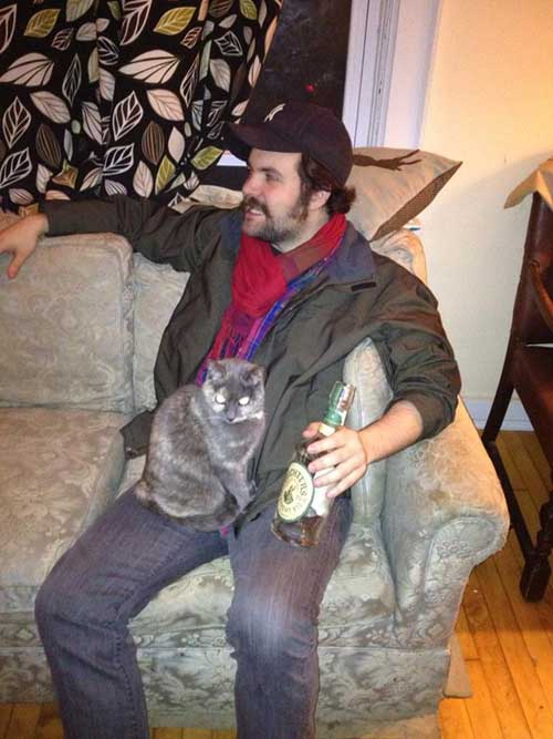 Filmmaker Josh Weissbach relaxes with a bottle of alcohol and his deaf and blind cat, Giblet.