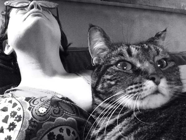 Lisa Barcy leans back on her couch while her cat Nellie rests on Lisa's stomach in this black and white photograph