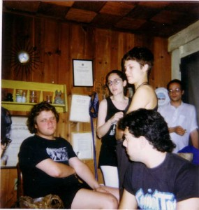 Bunch of people sitting and standing around a cramped indoor film set