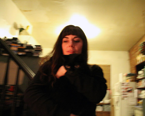 A slightly out of focus photo of Christine Lucy Latimer hugging her black cat Mingus
